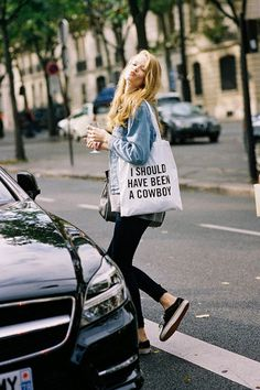 Shop this look for $394:  http://lookastic.com/women/looks/skinny-jeans-and-low-top-sneakers-and-duffle-bag-and-tote-bag-and-denim-jacket-and-longsleeve-shirt/2491  — Navy Skinny Jeans  — Black Low Top Sneakers  — Dark Green Leather Duffle Bag  — White Print Canvas Tote Bag  — Blue Denim Jacket  — Grey Longsleeve Shirt