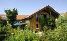 """Hier im """"Haus Natur"""" wurden Wohnen und Gewerbe im Einklang mit der Natur harmonisch zusammengeführt. Während im Wohnhaus auch das Büro untergebracht ist, befindet sich im Norden die Gewerbehalle dieses Gartenbaubetriebes.  Holzrahmenbauweise mit Deckleisten-Fassade aus Lärche natur"""
