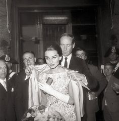 Ferrer helps Hepburn with her coat as they leave a Rome showing of The Nun's Story in 1959.