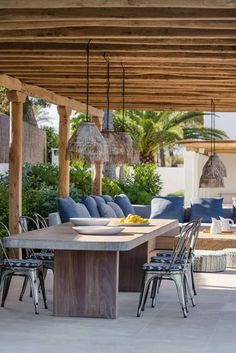 Mediterranean Outdoor Dining Area in Outdoor & Alfresco Dining Room Ideas. Metal chairs surround a wooden table and pendant lights hang in this outdoor dining area.