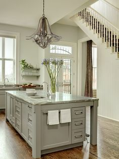 kitchen island - love the towel rack and the corner pedestals, straight lines on the cabinet fronts.