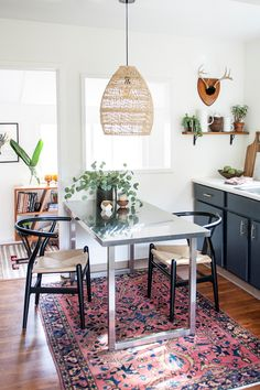Boho rattan pendant lighting over dining room table in kitchen with vintage Persian rug. Wishbone chairs. Ashley Redmond - The Tiny Treehouse - Interior Designer