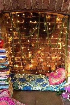 Turn a fireplace into a nook with string lights and pillows. | 21 Cozy Makeshift Reading Nooks
