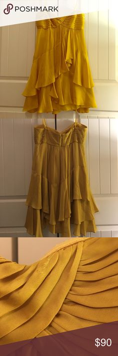 BCBG Maxazria silk cocktail dress BCBG Maxazria gold/yellowish silk cocktail dress.  Size 8.  Has a few pulls in the material pictures above. Not very noticeable unless pointed out.  Has been worn twice. Originally came with removable straps but no longer have the straps.  Dress is now only strapless.  Dress has been dry cleaned. Has button up back and zipper. BCBGMaxAzria Dresses