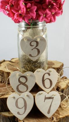 Table Numbers around mason jar, flowers wrapped in burlap. But different flowers.