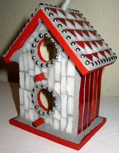 Adorable hand crafted red and white stained glass decorative birdhouse. Made with hand cut stained glass, ball chain, and light gray grout. Measures 4 1/4 x 3 1/2 x 2 1/2. Grout has been sealed, but not recommended for outdoor use.