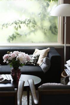 Tan/brown bad walls, black sofa, white trim.