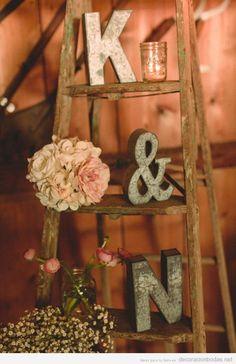Decoración de boda con escalera de madera e iniciales de los novios