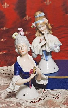 "TWO LARGE GERMAN PORCELAIN HALF DOLLS BY GOEBEL. (1) 5 ½"" doll known as ""Jenny Lind"", light brown hair with topknot and ringlet curls, headband, bow and flowers, black choker, floral bodice, holding rose, painted features with downward glancing eyes, incised Goebel trademark. (2) 5 ½"" doll in Marie Antoinette-style.  Incised ""Goebel"" Commentary: Very fine quality dolls in excellent condition."
