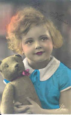 Antique photo of a beautiful child with her teddy bear.