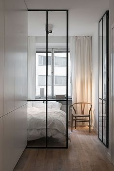 black steel + glass doors + wishbone chair + wood floors + white + bed nook