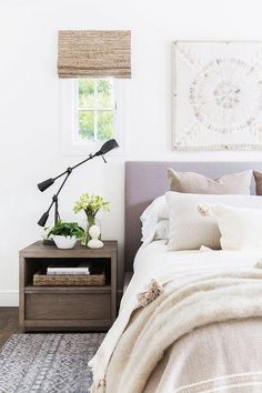 Alyssa Rosenheck - Amanda Barnes Interior Design - Window dressed in bamboo roman shades flank a carved wood art piece hung over a gray upholstered bed dressed in white and cream bedding.