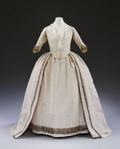 This robe and petticoat dating from 1779 is made of white silk woven with silver strip in a design of small silver leaves. It is decorated with a fringe made of strands of silver thread, strip and spangles, interspersed with tassels of the same materials. Find out more http://collections.vam.ac.uk/item/O127207/wedding-dress-unknown/