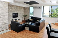 Open concept living area with rock wall, wood flooring, white ceiling, black leather furniture and mounted small flat screen television