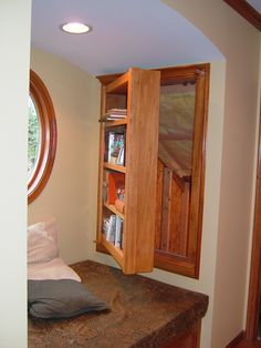 the bookcases on either side of the ohio window seat open up for access