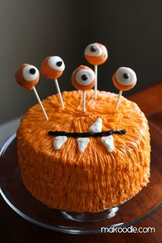 MONSTER CAKE a cake frosted with a star tip then cake pops dipped in orange icing then add eyes