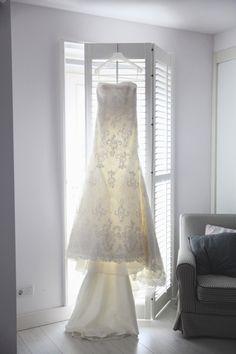 de mooie trouwjurk hangt voor het raam