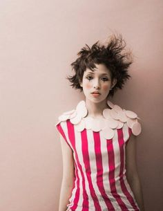 clown. pink background. white. dark pink stripes. circle collar. frizzy puffy brown hair.