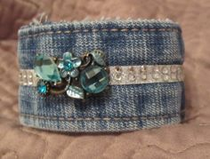 This cuff bracelet has been constructed from a wash denim waistband. The bracelet measures approximately 7 1/2 inches long when fastened and about 1 1/2 inches wide. It has a beautiful vintage look blue crystal bauble over a strip of crystal accents. Hook and loop closure.    Each one is different and has preserved the worn look of those old comfortable jeans. Raw edges intact and blinged out! The perfect accessory for a dressed up (or down) look. Great look for the tattered vintage grunge…