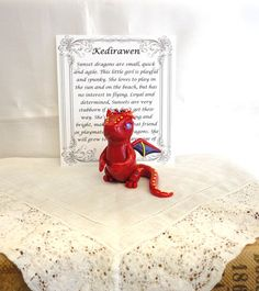 This is Kedirawen, she is a baby sunset dragon. This little girl is hand sculpted from polymer clay and sealed with a gloss glaze to add protection and shine. The card in the picture is included with her, it shows her name and gives a little description about her personality and characteristics according to dragon lore. Sunset dragons are small, quick, and agile. This little girl is playful and spunky. She loves to play in the sun and on the beach, but has no interest in flying. Loyal and…