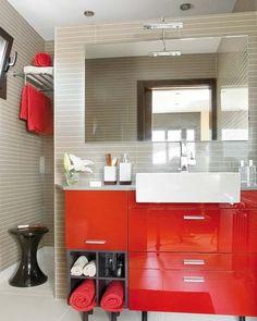 El frente del lavabo, en llamativo rojo, se apoya en el tabique que delimita la ducha