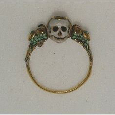 Memento Mori ring    Late 17th century    Gold ring, the bezel in the shape of a young woman's face on one side and a skull on the other, enamelled white with touches of red, and set with a diamond, the shoulders of the hoop lobed and richly chased and enamelled, set with small harlequin stones