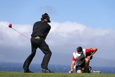 Bubba Watson pretends to tee off as his caddie Ted Scott holds a finger on the ball to keep it from blowing away on the 10th hole. (Christian Petersen/Getty Photo / January 6, 2013)