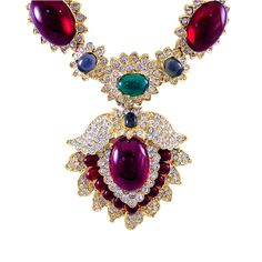 """FAMOUS Jackie Onassis KJL Necklace  US  1980s  This very famous necklace by Kenneth Lane has cranberry, emerald, blue moonstone and crystal rhinestones in a goldtone setting and was created in the l960's for his favorite client Jackie Onassis. Very much in demand, Ken keeps this beauty in his line reviving it every decade. This necklace measures 19"""" long with pressure closure; the front drop is 3 1/2"""" x 2 1/2"""". This necklace is signed Kenneth Lane."""