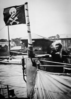 "The first known photo of a Jolly Roger. It is being flown from the main periscope of the Vickers Canada, Montreal-built submarine HMS H5 on returning to Great Yarmouth after sinking U-51 on 14 July 1916. The boat was commanded by Lt Cromwell H. Varley, RN, and the officer in the photo is Lt John Byron, RNR, the Navigator."" saoc-central.ca"