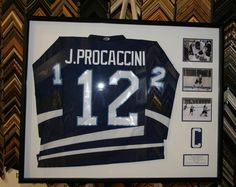 High School hockey jersey framed w/ pictures of him playing.