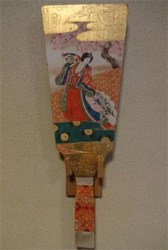 A woman dressed in junihitoe on a hagoita New Years paddle.