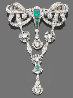 An emerald and diamond brooch/pendant  Of ribbon bow design, millegrain-set throughout with old brilliant and single-cut diamonds, decorated to the front with cut-cornered step and square-cut emeralds, suspending two articulated diamond swags, diamonds approx. 3.20ct. total, length 7.2cm. Edwardian or Edwardian style at best guess. Might be early, early Art Deco.