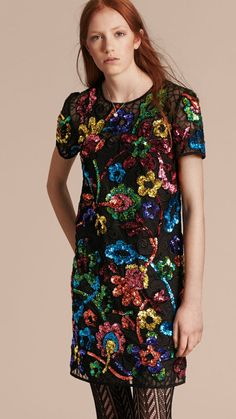 A sleeveless Burberry shift dress constructed from Italian guipure lace. The sparkling design is embellished with colorful floral appliqués that have been hand-sewn with glittering sequins.