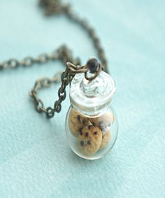 This necklace features a miniature glass cookie jar pendant adorned with handmade chocolate chip cookies sculpted from polymer clay. The miniature jar hangs on a bronze chain necklace that measures 24