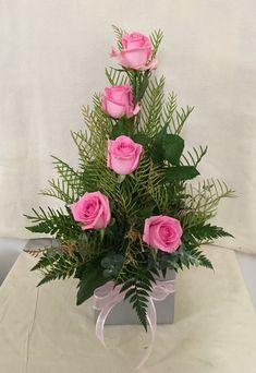 This arrangement is made with pink roses, leather leaf fern and parlor palm/ commodore palms. This arrangement has a silkytexture from the roses and a faned out/ pokey texture from the different palms.the pink tulips creates the height of the arrange Valentine Flower Arrangements, Modern Floral Arrangements, Flower Arrangement Designs, Church Flower Arrangements, Church Flowers, Valentines Flowers, Beautiful Flower Arrangements, Silk Flower Arrangements, Funeral Flowers