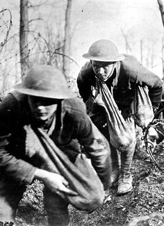 Soldiers advance into no-man's land with sacks of hand grenades. France, 1918.