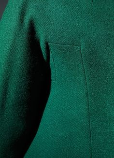 James placed a favored lyre-shaped seam on the suit jacket and mirrored its curve in the opposing cutaway front hem. The cropped front of the jacket then frames two of four splayed release darts from the waist of the skirt, which introduce ease to the zone of the abdomen and hips