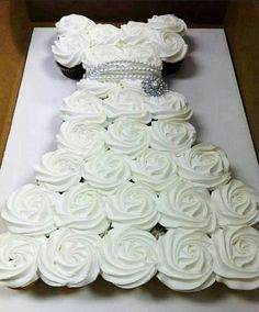 Different white topping cupcakes placed together to create the shape of a wedding dress, a great way to present your cupcakes in an elegant way. #Cupcakes #Wedding #Dress #Engagement #Party #White #Delicious #Elegant