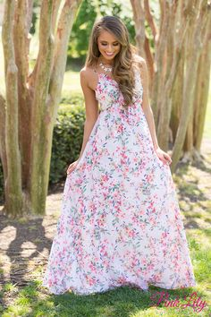 We adore this gorgeous new floral maxi dress! The floral pattern features shades of pink, green, purple, and white for a lovely look, while the cute front tie and the ruffled look along the v-neck add even more feminine touches!
