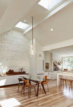 white & wood, modern rustic dining room & kitchen, skylights, white brick walls, contemporary glass dining room light