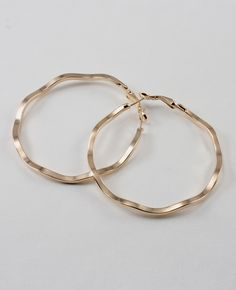Minimal yet attractive update to a classic.  These fluently oversized hoop earrings feature a effortlessly wavy shape with clip-back closure.<br /><br />- MEASUREMENTS: 2