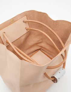 Mid-size vegetable tanned supple leather tote bag from Jujumade. Unlined, with handmade stoneware details and leather cord straps. • Vegetable tanned leather • Unlined • Leather cord straps • Includes raffia storage bag • Stoneware strap detai