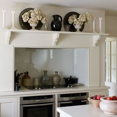 The shelf with its carved brackets plays host to a perfectly symmetrical tableau of pretty objects.