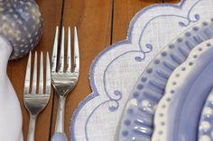Em azul e branco, jogos americanos e guardanapos em linho bordados nos exatos tons da louça.