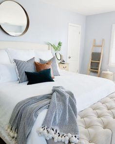This pale blue bedroom uses a round mirror to reflect natural sunlight.