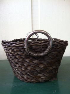 Wicker woven basket with silver handles. Unusual basket, tightly woven, well-constructed. Silver handles accentuate the darker basket color....