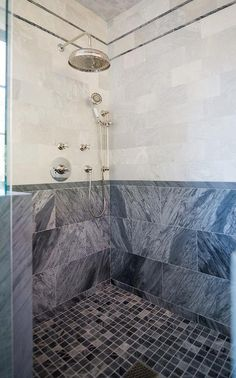 Master bath shower boasts white marble tiles accented with gray marble pencil tiles on upper walls and gray marble tiles, Bardiglio Marble, on lower walls accented with a polished nickel shower kit alongside a blue marble grid tile shower floor.