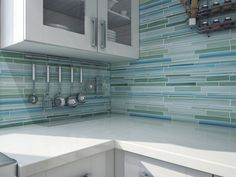 Modern Kitchen with Green Blue Glass Peel Stick Mosaic Backsplash, Wooden White Painted Cabinet Door Glasses, and Stainless Steel Wall Mounted Kitchen Utensil Organizer