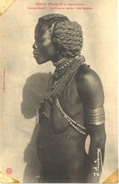Translated caption reads: ''French Congo and Territories - Banziri woman- Hairstyle made with pearls called Bayakas ''. Profile of a woman wearing bracelets and bead and shell necklaces. Congo Français. Photograph by J. Audema. ca 1905