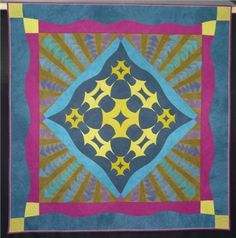 Harlequin by Gwenfai Rees Griffiths. Amish quilt influence. Curved churn dash medallion and flying geese. Photo by Katy at Popular Patchwork